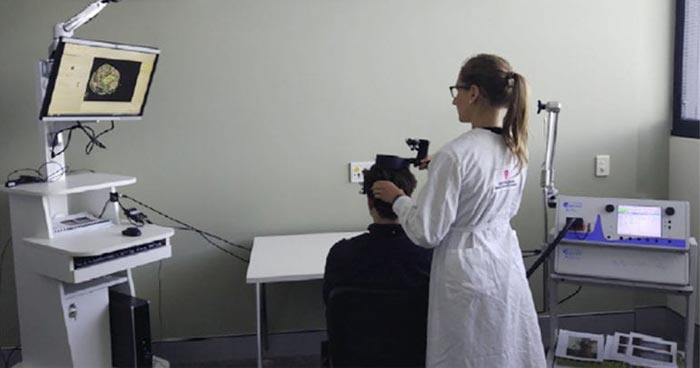 Researcher using instrument to analyse man's brain