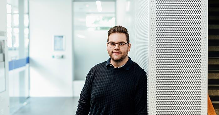 Mark Dorsett standing in modern corridor