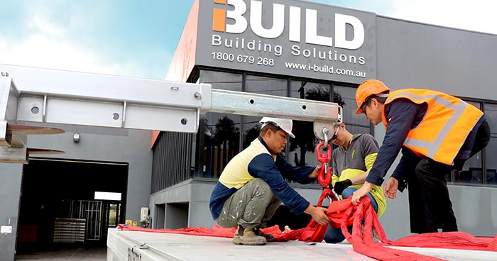Workers loading equipment on to a truck with iBuild building in the background