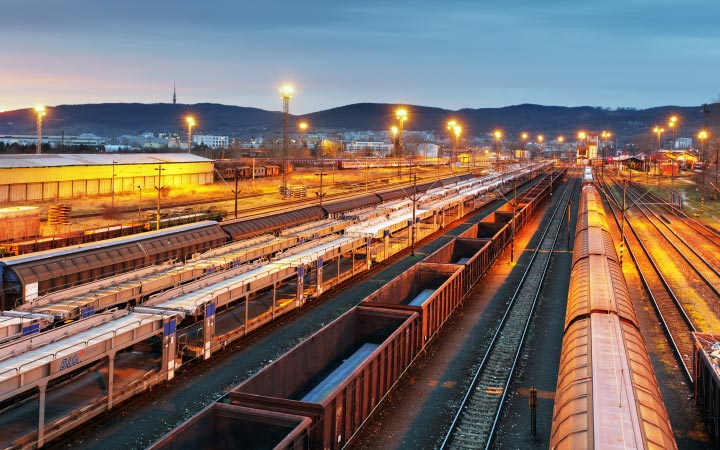 Railway yard at dusk, looking down on rows of parked freight trains