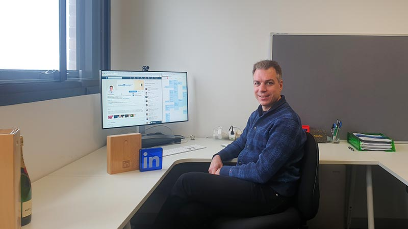 Uwe Aickelin sitting at a desk in his office with LinkedIn Spotlight trophy