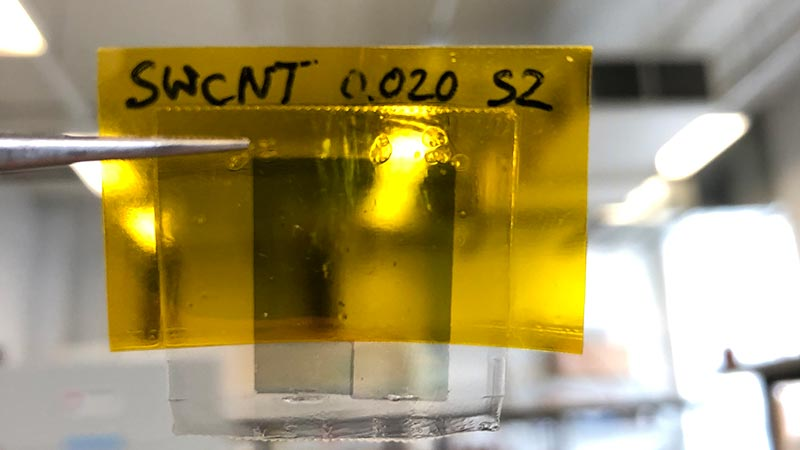 A yellow sample of the polymer being held up with lab in background