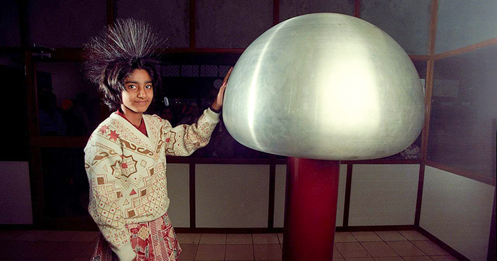 Girl touching Van der Graaf generator with hair spiked up due to electrical charge