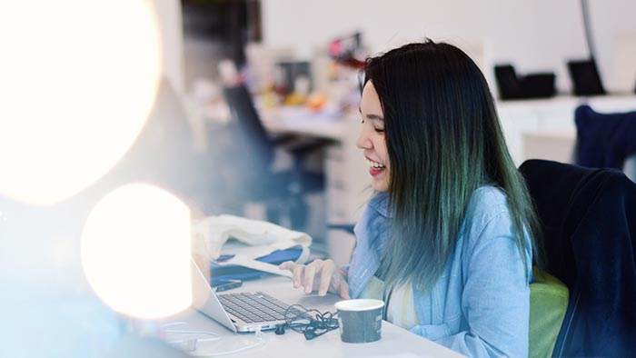 Young woman at desk using laptop with lens flare in foreground