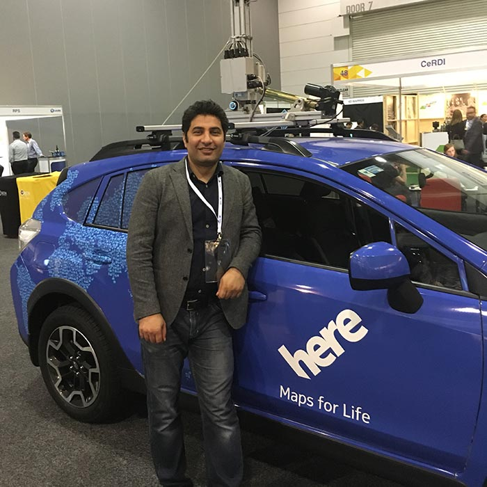 Ali standing in front of blue HERE branded car