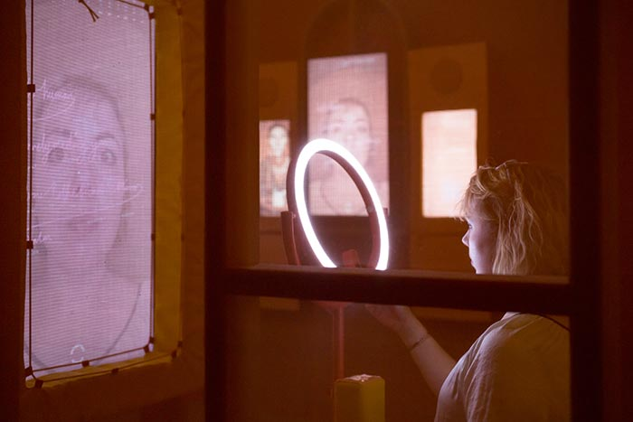 Woman in Biometric Mirror looking into ring light with face displayed on screen in front of her