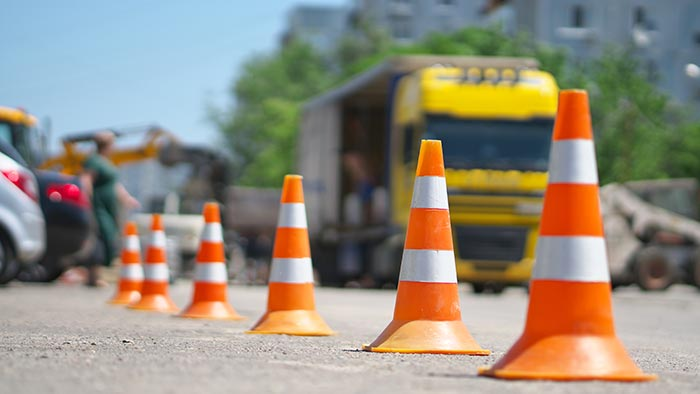 Row of traffic cones with blurred trucks in background