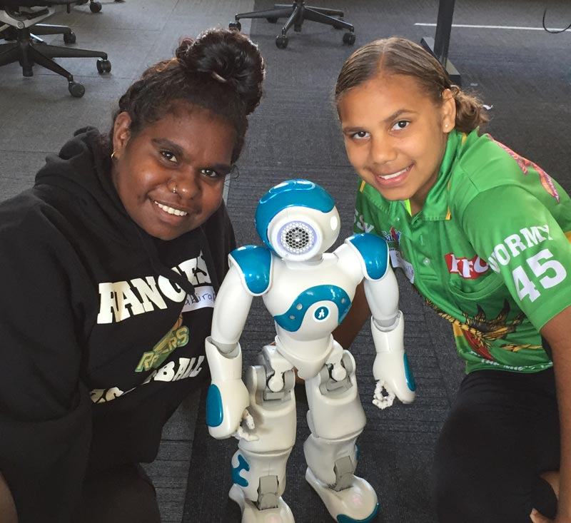 Two girls pose with a robot