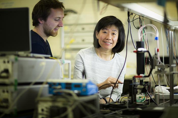 Professor Christina Lim with fellow researcher in photonics laboratory