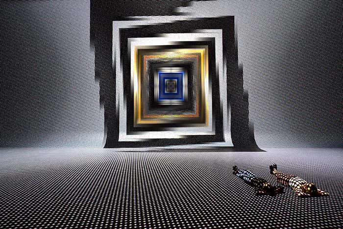 Two people lying on floor with dot grid projected over them and square spiral portal art on wall