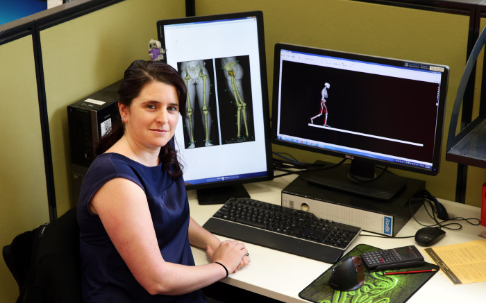 Elyse sits in front of computer screens displaying skeletal figures