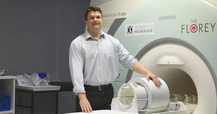 Associate Professor Andrew Zalesky standing by MRI