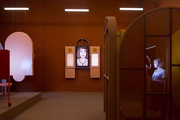 Woman in Biometric Mirror booth with screen displaying her face on wall