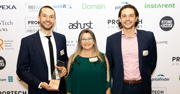 Exergenics cofounders standing in front of a sponsor branded wall at Proptech Association of Australia award dinner