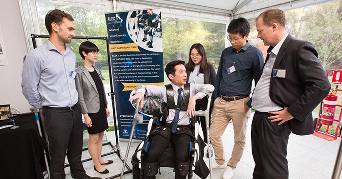 ALEX team demonstrating exoskeleton to Dean Mark Cassidy